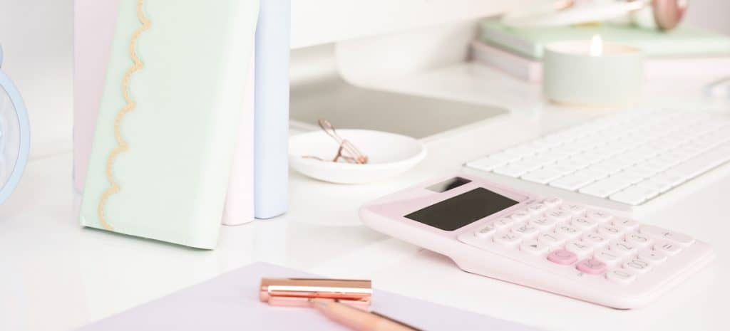 pink calculator on desk with pen