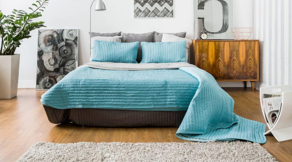 image of a beautiful blue bed used as the featured image for the post on how to become an airbnb host