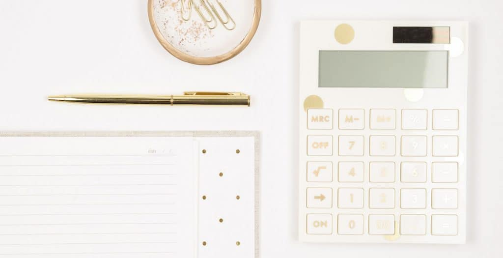 desk with a gold calculator for the featured image in the post difference between rich and wealthy