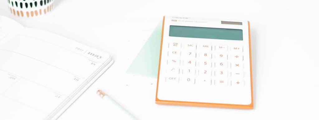 white calculator on a desk used as featured image for the digit vs acorns app review