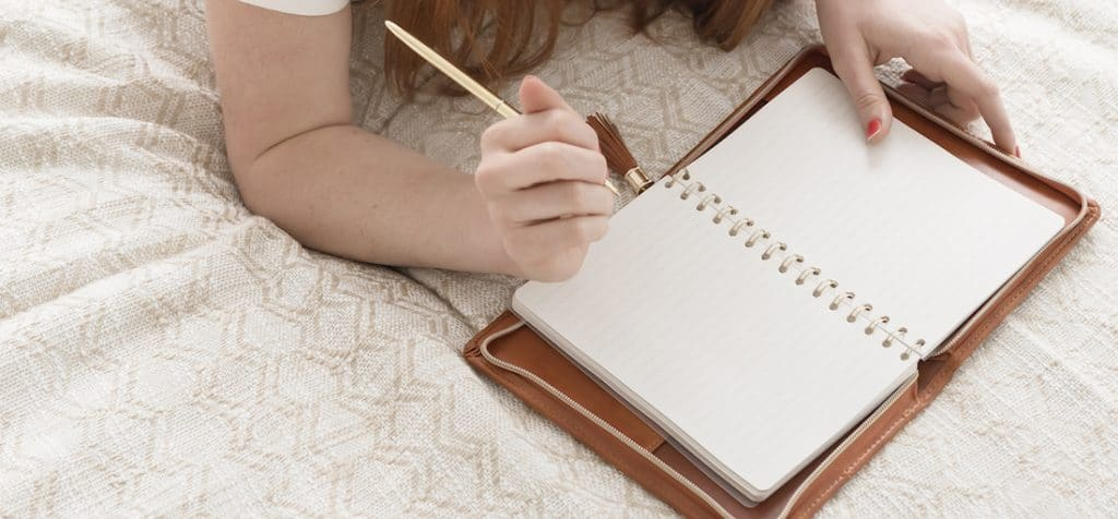 woman laying on bed writing in notebook used as featured image in grammarly review