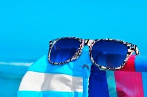 Pair of knock of Ray-Ban sunglasses on the beach.