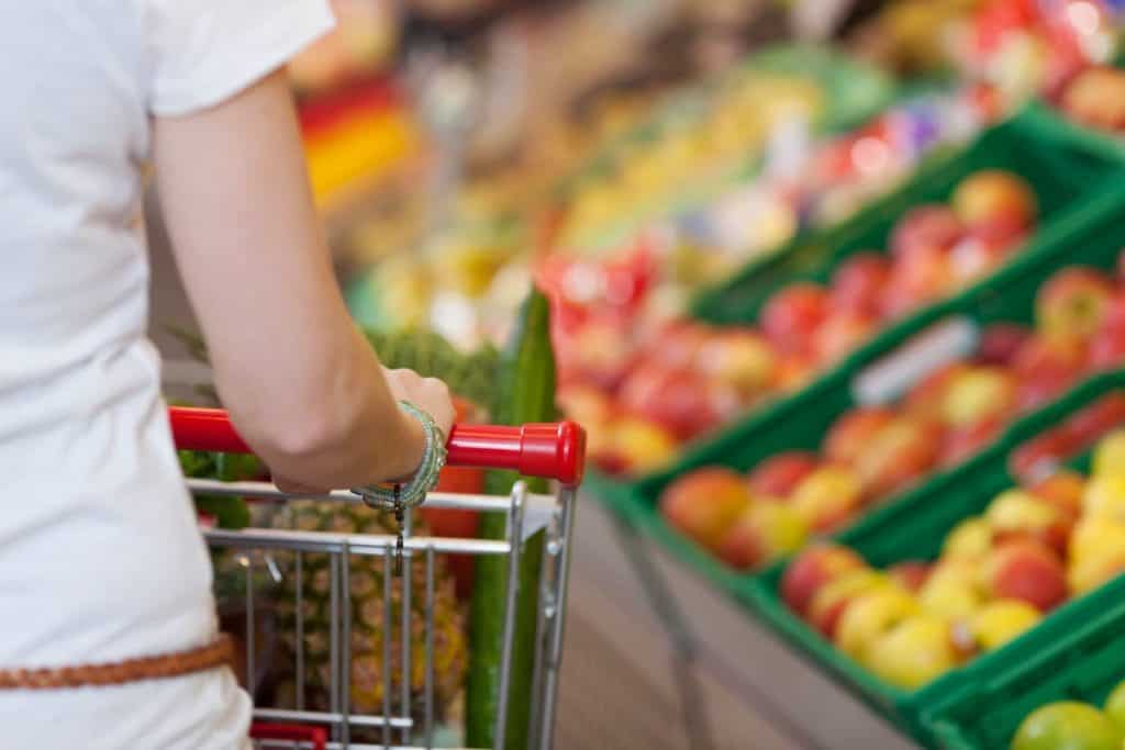 Woman at the grocery store shopping with her cheap grocery list