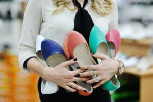 woman holding colorful ballet flats that look like tieks knockoffs