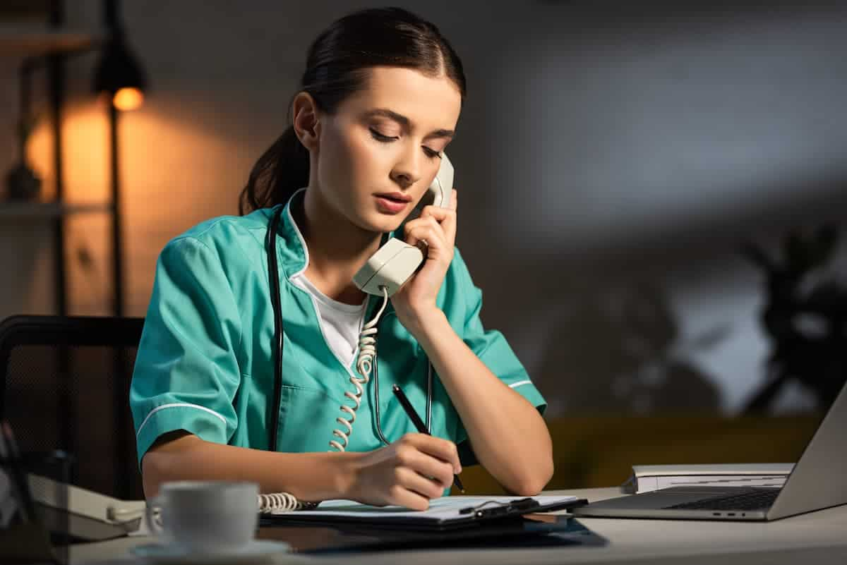 nurse working from home with laptop and phone